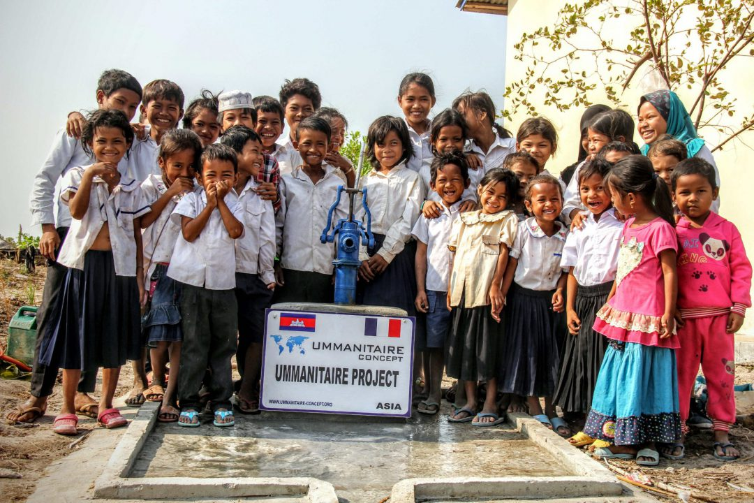 enfants souriants autour d'un puits d'eau potable